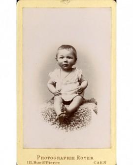 Bébé en chemise, assis, portant une chaîne avec croix au cou