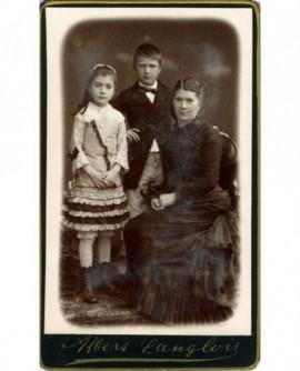Femme en robe à tournure assise et ses deux enfants debout (garçon et fille)