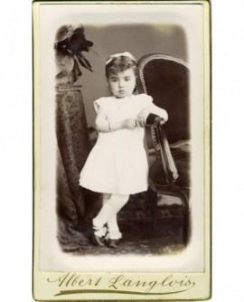 Fillette en robe blanche debout, accoudée à un fauteuil