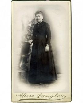 Jeune femme en robe noire debout accoudée à un fauteuil