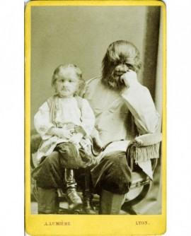 Personnages de foire: un adulte gorille tenant un enfant sur ses genoux