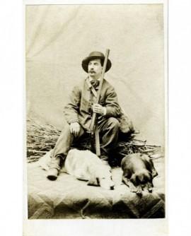 Chasseur moustachu assis sur un fagot, 2 chiens couchés à ses pieds