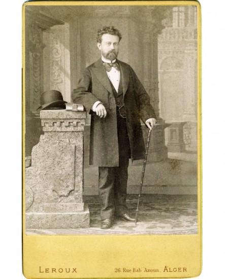 Homme barbu accoudé avec chapeau melon et canne