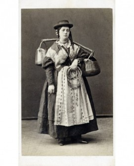 Femme en costume traditionnel, coiffée d'un chapeau masculin, debout, un jouquet avec deux chaudrons