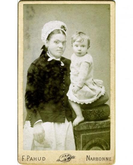 Nourrice en coiffe tenant un jeune enfant (assis sur une stèle)