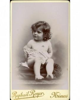 Bébé en chemise, épaules dénudées, assis sur un coussin