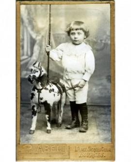 Garçonnet debout, une lance à la main, près d'un cheval de bois