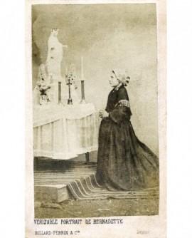 Bernadette Soubirous (en paysanne) à genoux devant un autel de la Vierge