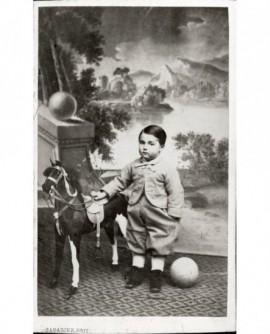 Garçon devant une toile peinte, avec cheval à rouletet et ballon (jouet)