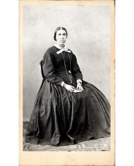 Femme en robe assise, un livre sur les genoux