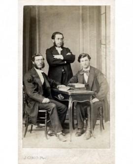 Trois hommes autour d'une table avec livres