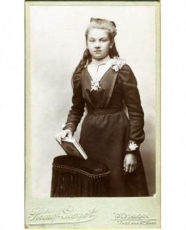 Jeune fille debout, tenant un livre sur la tranche