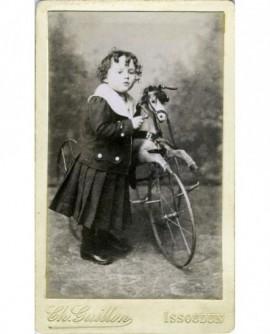 Enfant en robe noire à col marin devant un cheval de bois (jouet)