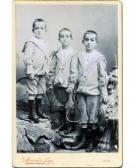 Trois enfants en col marin avec raquettes et cerceau. jouet