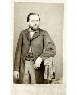 Portrait d'un homme barbu en manteau, accoudé sur un siège