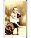 Jeune enfant, en chemise, accoudé à un fauteuil