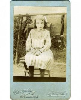 Fillette en robe blanche assise sur une chaise de jardin