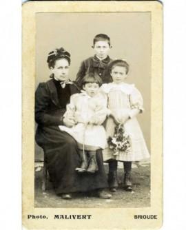 Femme en chapeau assise avec trois enfants