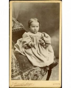 Bébé en robe pied de poule assis, un biscuit à la main