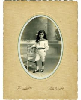 Fillette debout en chemise à col marin, appuyée sur une chaise