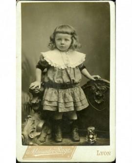 Petite fille en robe à col de dentelle, debout sur un banc