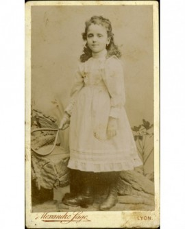 Petite fille en robe blanche debout, une raquette à la main