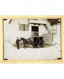 Militaire assis dans un attelage, le cheval tenu en bride par un valet en costume