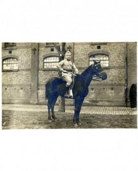 Militaire (en kaki) à cheval dans la cour d'une caserne