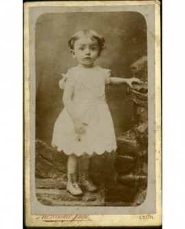 Petite fille en robe blanche sans manches, debout sur rochers factices
