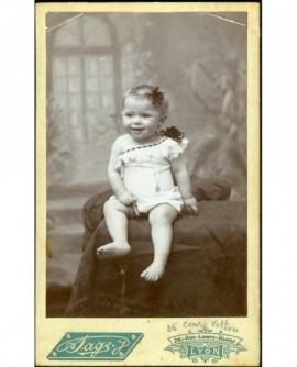 Bébé en chemise, éâule dénudée, assis souriant