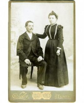Couple : homme moustachu assis, femme debout appuyée sur lui