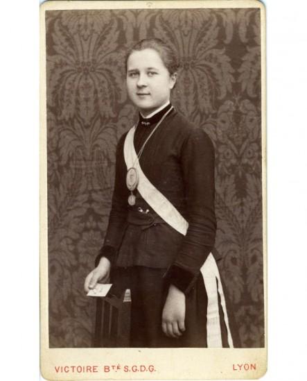 Jeune femme debout,médaille et écharpe au cou: suffragette ?