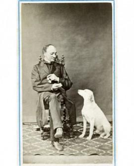 Homme en manteau assis, ses lunettes à la main, tendant à manger à son chien