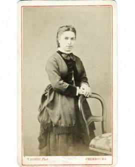 Jeune femme en robe à fronces debout, appuyée sur une chaise