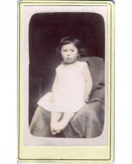 Enfant en chemise assis dans un fauteuil