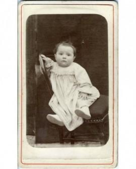 Bébé en robe assis sur une chaise