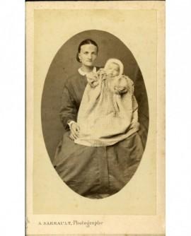 Femme assise, un bébé en bonnet et robe longue sur les genoux