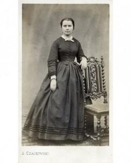 Jeune femme en robe debout, accoudée à une chaise
