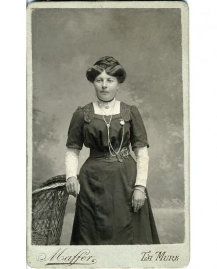 Femme en robe debout, appuyée sur un fauteuil en rotin