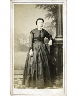Femme en robe debout, accoudée à une colonne