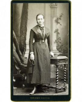 Femme en robe debout, médaille au cou, cordon avec ponpons à la main