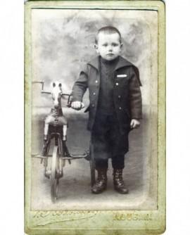 Petit garçon debout tenant un cheval de bois-tricycle