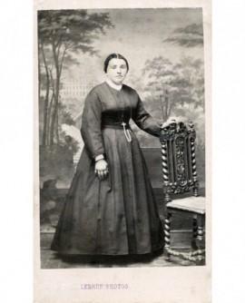 Jeune femme en robe debout appuyée à une chaise