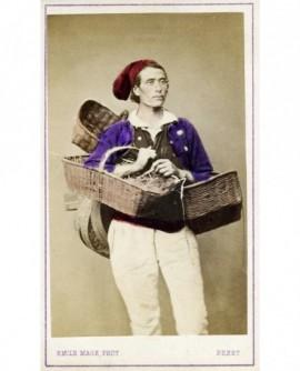 Homme de Plougastel en bonnet rouge, gilet mauve et pantalon blanc , les bras chargés de paniers