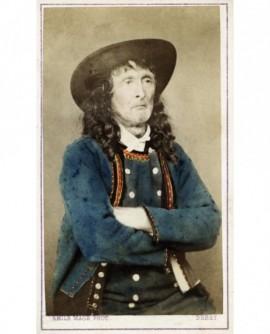 Homme à cheveux longs en costume breton de Pont-Croix, bras croisés