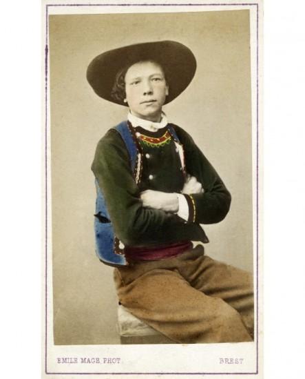 Jeune homme de Quimper en costume breton assis, bras croisés