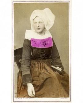 Femme de Chateaulin en costume breton assise, un livre à la main