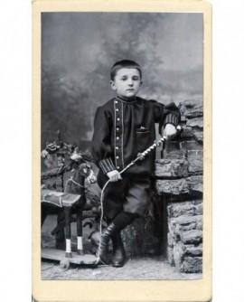 Enfant debout avec cheval à roulette et fouet. jouet