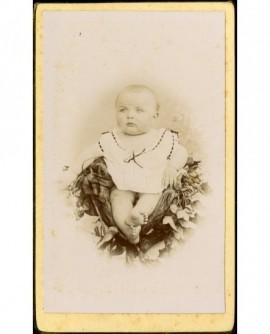 Bébé sans cheveux, en chemise, assis