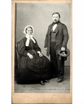 Couple âgé: femme en bonnet blanc assise, homme debout gibus à la main